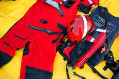 Diver Firefighter Wetsuit Emergency Rescue Kit. Diver firefighter team emergency water rescue survival kit with orange wetsuit and safety helmet along United royalty free stock photos