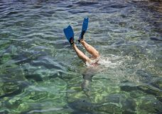 Feet of diver in fins above the surface of the sea. Diver flipper dive into the blue transparent sea. Feet of a diver in blue fins above the surface of the sea Royalty Free Stock Photo