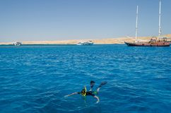 A diver floats in the sea. Near yachts Royalty Free Stock Image