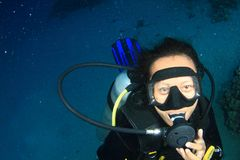 Diver - girl underwater. Tropical girl - young Indonesian woman dressed up into wetsuit and BCD scuba diving in sea with mask and regulator, swimming in Red Sea stock image