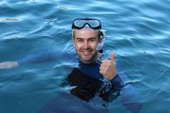 Diver giving a thumbs up after an immersion.  stock image