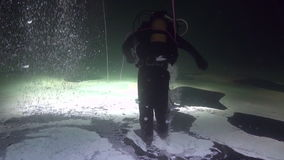 Diver goes on ice underwater of White Sea. stock footage