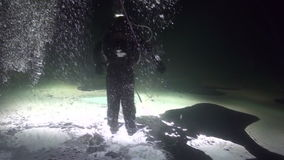 Diver goes on ice underwter of White Sea. Creative diving and dangerous extreme sport. Unique shooting stock footage