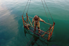 Diver in heavy spacesuit. Diver in heavy spacesuit plunges into the sea Royalty Free Stock Photo