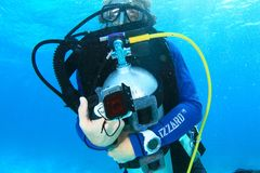 Diver hugging bottle. Scuba diver guide in blue wetsuit and mask hugging bottle with BCD in blue sea in Raja Ampat, Papua Barat, Indonesia stock photo