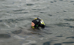 Diver on lake. Diver swim on dark wate of lake Stock Photography