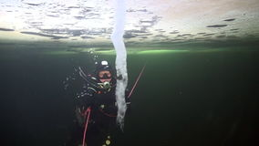 Diver near icicle on double bottom underwter in ice of White Sea. Creative diving and dangerous extreme sport. Unique shooting stock video footage