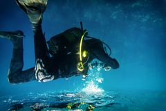 The diver and reflection. ю Diver floats in weightlessness above the water surface Stock Photo