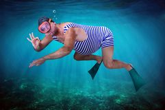 Diver in retro swimsuit. Swims underwater and shows gesture O.K. Swimmer examines the seabed. Vacation at sea. Man snorkeling in the tropical sea. Vintage style royalty free stock photo