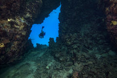 Diver silhouetted in blue cavern Royalty Free Stock Photography