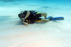Diver Sleeping on Sandy Sea Bottom Royalty Free Stock Photo