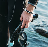 Diver with snorkel mask. Close-up of diver male hand with snorkel mask on background of sea Stock Photo