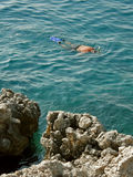 Diver and stone. Diver in blue sea near the rock coastline Stock Photo