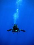 Diver swimming with buoy. Attached to a rope Royalty Free Stock Images