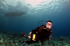 Diver swimming under the boat Royalty Free Stock Images