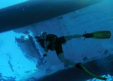 Diver Swimming under Catamaran Stock Photo