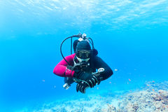 Diver swimming under water. Male scuba diver swimming under water Stock Photos
