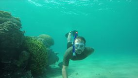 Diver swims along a coral reef
