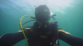 Diver under water. Diver in equipment with regulator in mouth under the water. Face diver in mask close-up stock footage