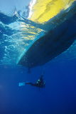 Diver Underwater. A diver underwater below a diving boat Royalty Free Stock Images