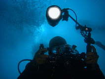 Diver with underwater camera and light. A diver with a large underwater camera and professional light Royalty Free Stock Photography