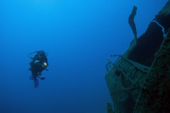 Diver underwater - deep water. A scuba diver is exploring an ship-wreck in deep blue water stock image
