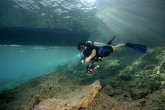 Diver underwater, Diveboat & sunbeams. A female scuba diver with a torch in her hand is swimming below a diveboat. Boat and sunbeams in the background royalty free stock images