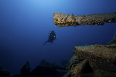 Diver underwater with ship. A scuba diver is exploring an ship-wreck in deep water royalty free stock photography