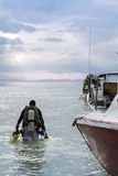 Diver. A diver walking towards the ocean with some empty boats beside him Stock Image