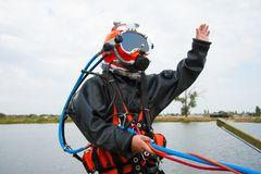 Diver in a diving suit and helmet ready to dive. Diver in the water in a diving suit and helmet ready to dive royalty free stock photography
