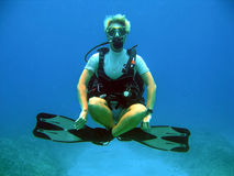 Diver weightless underwater. Woman diver displays excellent buoyancy skills and floats weightless underwater on a sunny dive Royalty Free Stock Photography