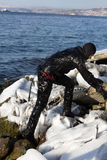 Diver working in difficult Arctic conditions. diver in black dry suit climbs on icy stones,. RUSSIA, Kamchatka - December 13, 2011: Diver working in difficult Royalty Free Stock Photography