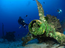 Diver in wreck. Diver in rusty wreck on sea floor with swimming fish Royalty Free Stock Photo