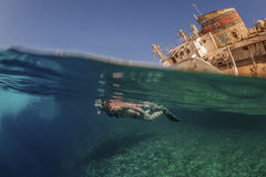 Diver with wreck. Diver swimming along a wreck in the Red Sea Stock Photo