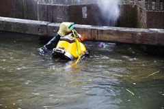Diver with yellow helmet working in dirty water at the shore rei Royalty Free Stock Photography
