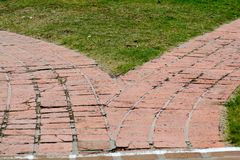 Divergent brick paths in teh grass. A red brick path diverges into two leading in different directions Stock Photo