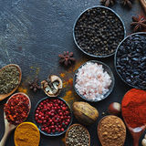 Divers épices, écrous et herbes indiens dans les cuillères et des cuvettes en bois en métal Photos stock