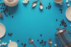 Divers accessoires à café : Presse de café, tasses, soucoupes, grains de café, cuillères et sucre français sur le fond de papier  photos stock