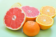 Divers agrumes : pamplemousse, orange, citron et mandarine sur un fond vert Photo stock