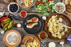 Divers casse-croûte américains traditionnels avec les jambes de poulet grillées et les pommes de terre frites sur la table de sal Image stock