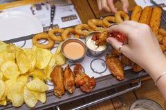 Divers casse-croûte en bière : pépites de poulet, puces, anneaux d'oignon, ailes de poulet frit sur une table en bois dans un bar Photos libres de droits