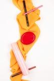 Divers cosmétiques sur une écharpe jaune d'isolement Image stock