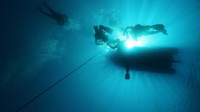 Divers in decompression stop. Divers in backlight during a decompression stop under the boat stock video footage