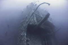 Divers on a deep underwater shipwreck Stock Photos