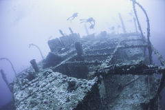 Divers on a deep underwater shipwreck Royalty Free Stock Photos
