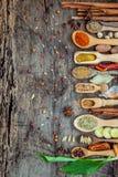 Divers des épices et des herbes dans des cuillères en bois Configuration plate des épices Photographie stock