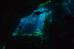Divers exploring hidden reefs in underwater cave Royalty Free Stock Photography