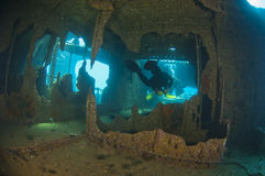 Divers exploring a large shipwreck Stock Images