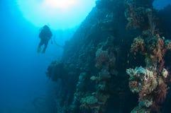 Divers exploring a large shipwreck Royalty Free Stock Photos