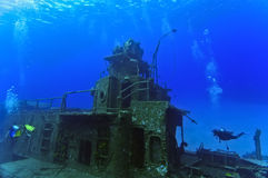 Divers exploring a shipwreck. Two divers are exploring the superstructure of the sunken wreck, the Tibbetts, a Russian frigate that was sunk in the waters off Royalty Free Stock Images